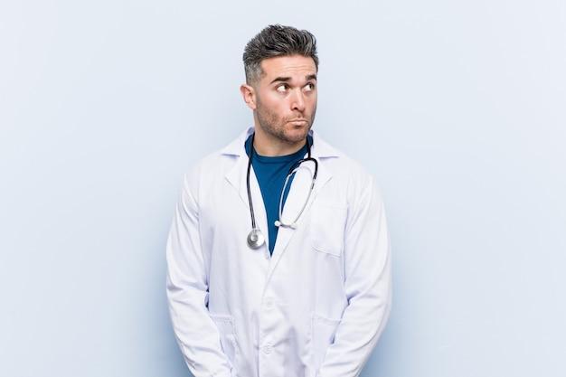 Junger hübscher doktormann verwirrt, fühlt sich zweifelhaft und unsicher.