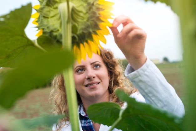 Junger hübscher erfahrener agronom im sonnenblumenfeld, der erntequalität prüft