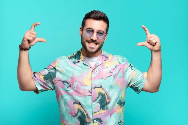 Junger hübscher erwachsener mann, der eigenes lächeln mit beiden händen umrahmt oder umreißt, positives und glückliches wellness-konzept aussehend