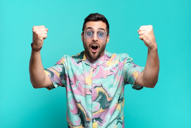 Junger hübscher erwachsener mann, der einen unglaublichen erfolg wie ein gewinner feiert, aufgeregt und glücklich aussehend sagt, nimm das!