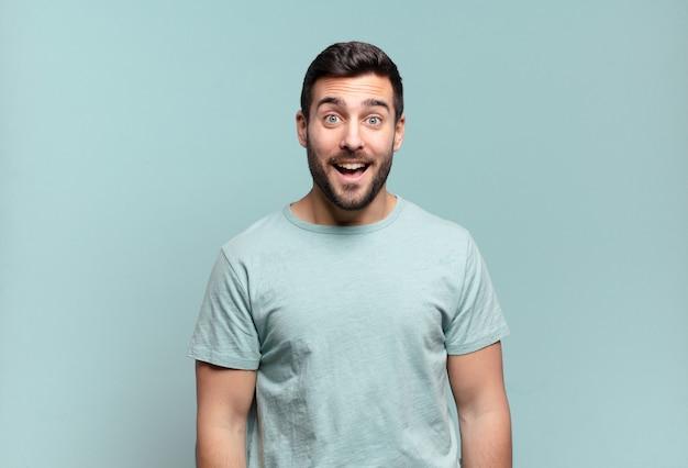 Junger hübscher erwachsener mann, der glücklich und angenehm überrascht aussieht, aufgeregt mit einem faszinierten und schockierten ausdruck