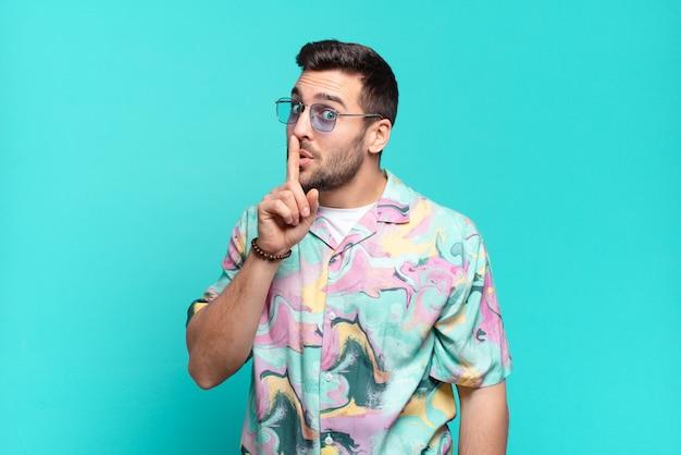 Junger hübscher erwachsener mann, der um stille und ruhe bittet, mit dem finger vor dem mund gestikulierend, shh sagt oder ein geheimnis hält