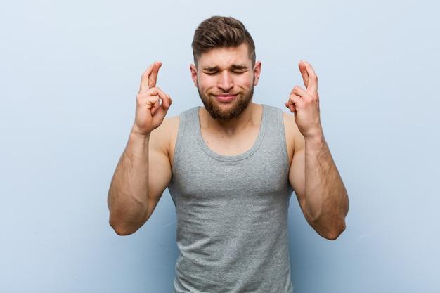 Junger hübscher fitnessmann, der finger für glück kreuzt