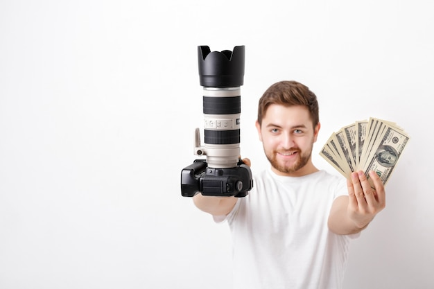 Junger hübscher fotograf mit bart in einem weißen hemd, das eine kamera und hundert-dollar-scheine hält. bezahlung für das fotoshooting