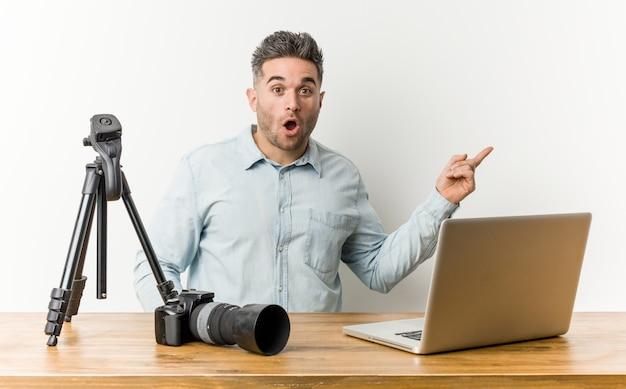 Junger hübscher fotografielehrer, der auf die seite zeigt