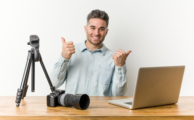 Junger hübscher fotografielehrer, der beide daumen oben, lächelnd und überzeugt anhebt