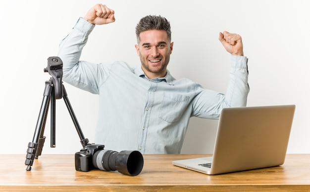 Junger hübscher fotografielehrer, der stärkegeste mit den armen, symbol der weiblichen energie zeigt