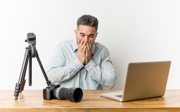 Junger hübscher fotografielehrer, der über etwas, mund mit den händen bedeckend lacht.