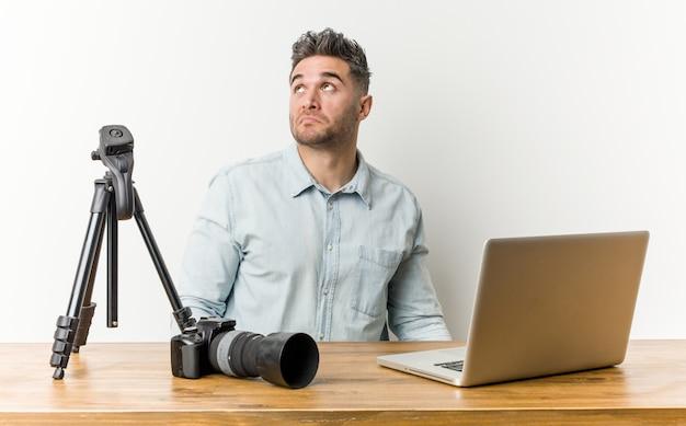 Junger hübscher fotolehrer, der davon träumt, ziele und zwecke zu erreichen