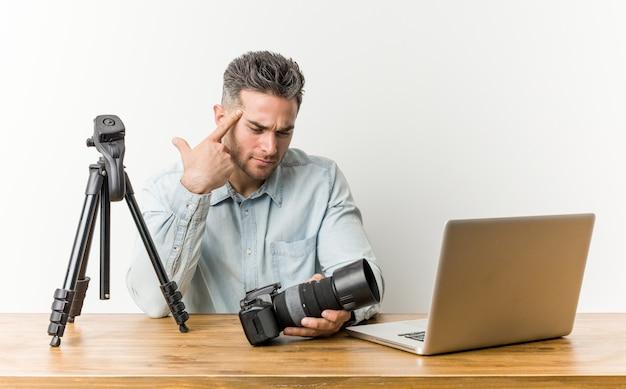 Junger hübscher fotolehrer, der eine enttäuschungsgeste mit zeigefinger zeigt.