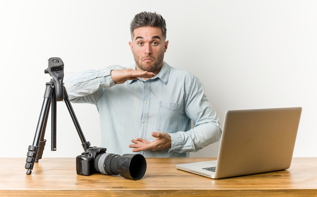 Junger hübscher fotolehrer, der etwas mit beiden händen hält