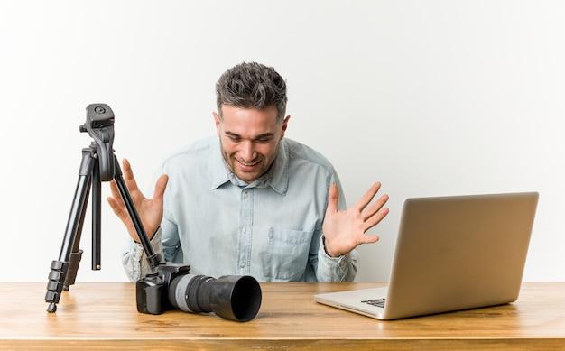 Junger hübscher fotolehrer, der freudig viel lacht