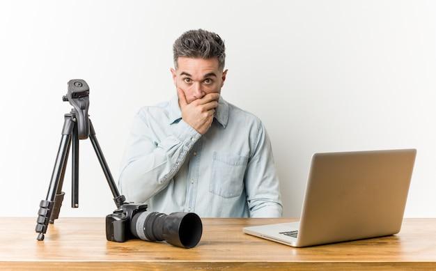 Junger hübscher fotolehrer, der nachdenklich zu einem leeren raum schaut, der mund mit hand bedeckt.