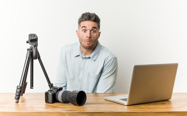 Junger hübscher fotolehrer zuckt mit den schultern und die offenen augen, die verwirrt werden.