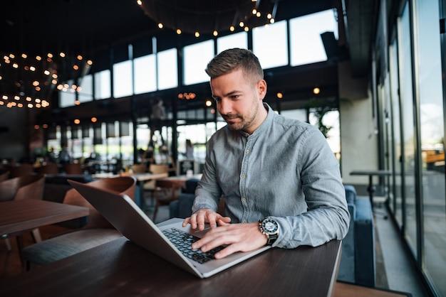 Junger hübscher freiberufler, der an laptop im modernen café arbeitet.