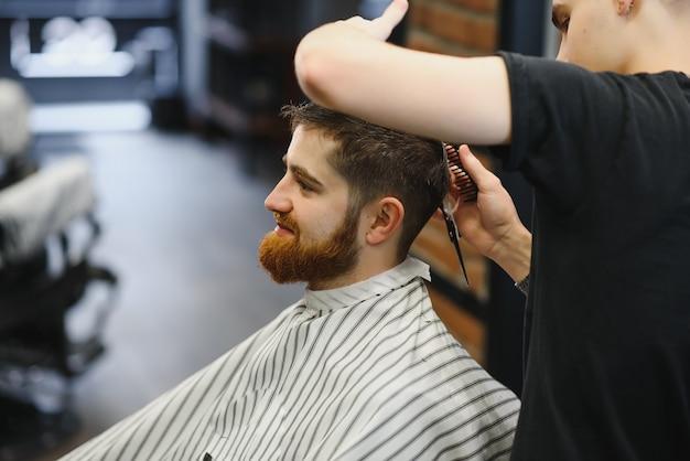 Junger hübscher friseur, der haarschnitt des attraktiven bärtigen mannes im friseursalon macht
