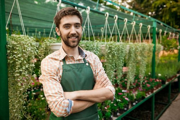 Junger hübscher fröhlicher gärtner, der lächelt und mit verschränkten armen zwischen blumen aufwirft