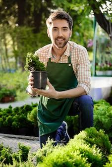 Junger hübscher fröhlicher gärtner, der lächelt und sich um blumen kümmert