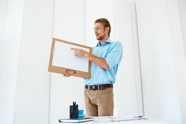 Junger hübscher fröhlicher geschäftsmann, der am tisch steht und hölzerne zwischenablage mit weißem blatt zeigt, das darauf zeigt. leichte moderne büroeinrichtung