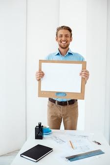 Junger hübscher fröhlicher lächelnder geschäftsmann, der am tisch steht und hölzerne zwischenablage mit weißem blatt hält. leichte moderne büroeinrichtung
