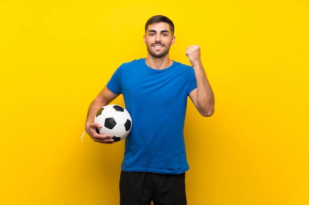 Junger hübscher fußballspielermann über der lokalisierten gelben wand, die einen sieg feiert