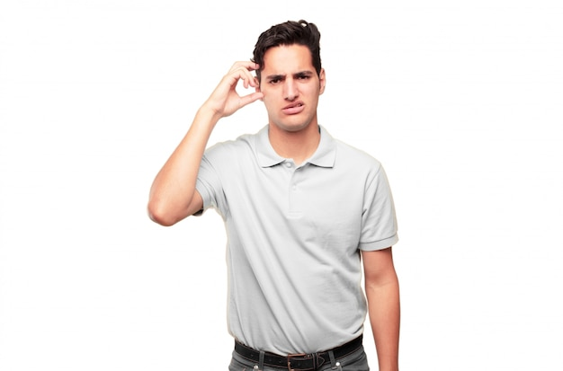 Junger hübscher gebräunter mann mit einem doof, dummen, dummen blick, gefühl entsetzt und an einem kürzlich r verwirrt
