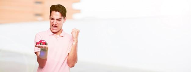 Junger hübscher gebräunter mann mit einem roten automodell