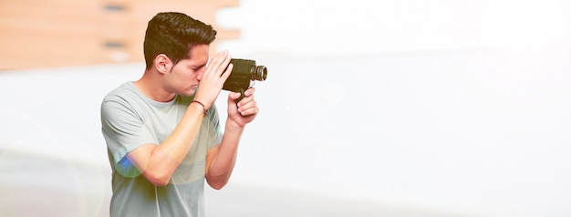 Junger hübscher gebräunter mann mit einer weinlesekinokamera