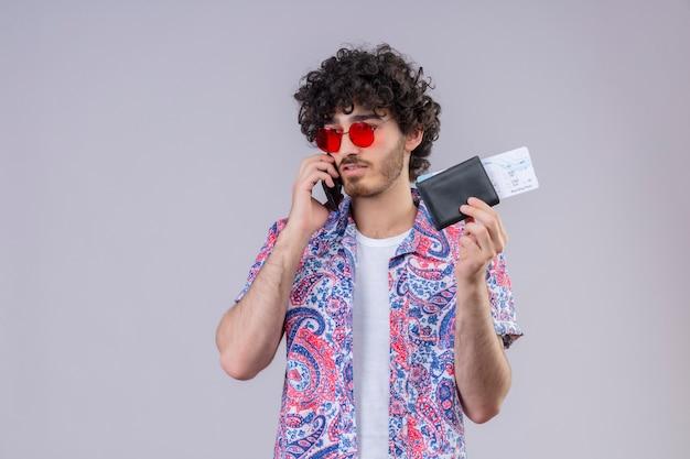 Junger hübscher gelockter reisender mann, der am telefon spricht, das sonnenbrille hält, die brieftasche und flugtickets auf isolierter weißer wand mit kopienraum hält