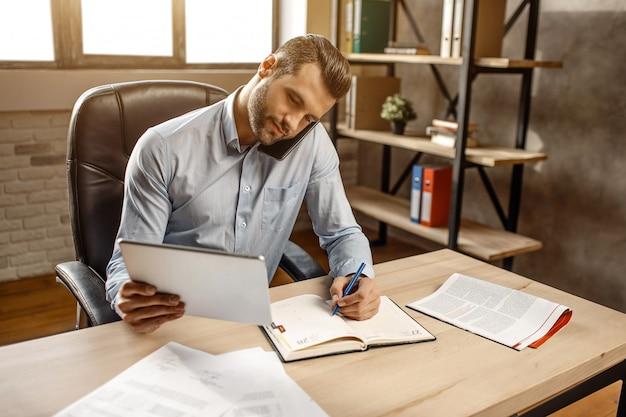 Junger hübscher geschäftsmann arbeitet in seinem eigenen büro. er sitzt am tisch und telefoniert. auch kerl verkabelung in dokumenten. beschäftigt. arbeitszeit. tageslicht.