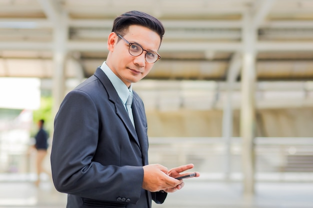 Junger hübscher geschäftsmann asiens mit seinem smartphone, der auf gehweg der modernen stadt steht.