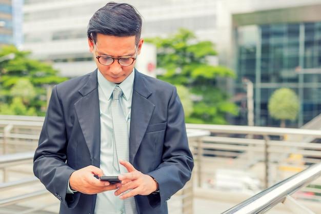 Junger hübscher geschäftsmann asiens mit seinem smartphone, der auf gehweg der modernen stadt steht
