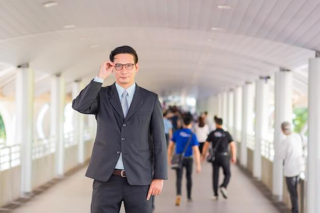 Junger hübscher geschäftsmann asiens mit seinen gläsern, die auf gehweg der modernen stadt stehen.