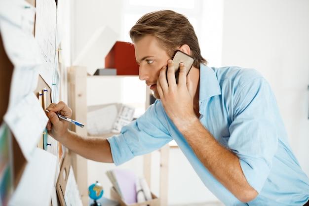 Junger hübscher geschäftsmann, der an dem papier schreibt, das an die pinnwand geheftet wird und am telefon spricht.