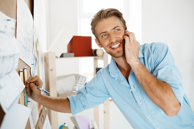 Junger hübscher geschäftsmann, der an dem papier schreibt, das an pinnwand angeheftet wird und am telefon lächelnd spricht.