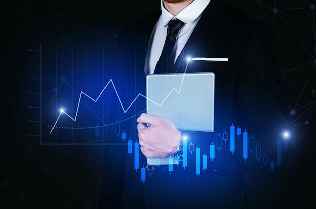 Junger hübscher geschäftsmann, der bewegliche intelligente tablette mit linkverbindung des globalen netzwerks des effektes und diagrammdiagramm des grafischen diagramms der börse hält