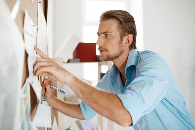 Junger hübscher geschäftsmann, der finger zeigt und auf das papier schreibt, das an pinnwand geheftet wird.