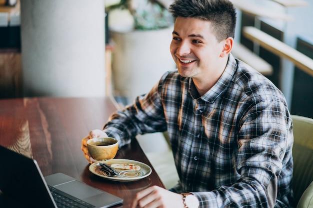 Junger hübscher geschäftsmann, der laptop in einem café verwendet