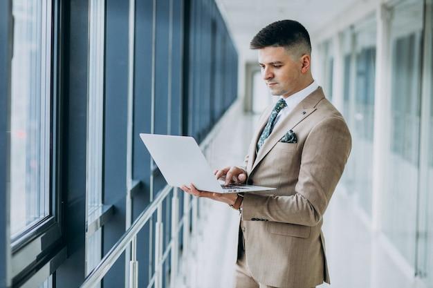 Junger hübscher geschäftsmann, der mit laptop im büro steht
