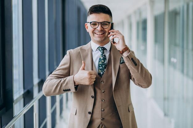 Junger hübscher geschäftsmann, der mit telefon im büro steht