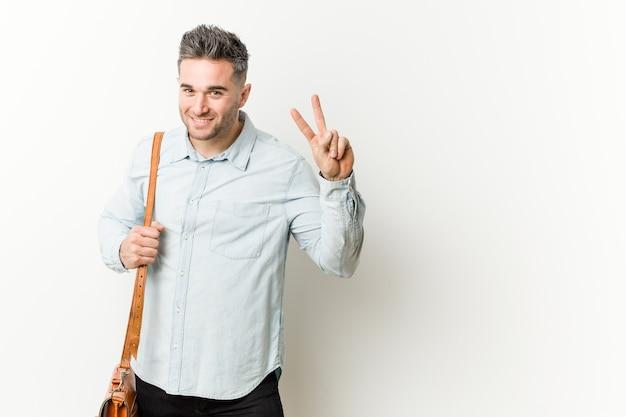 Junger hübscher geschäftsmann, der nummer zwei mit den fingern zeigt.