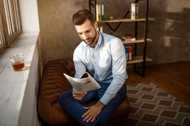 Junger hübscher geschäftsmann, der tagebuch in seinem eigenen büro liest. er sitzt am fenster und liest tagebuch. ein glas whisky steht auf der fensterbank. sonnenlicht an der wand.