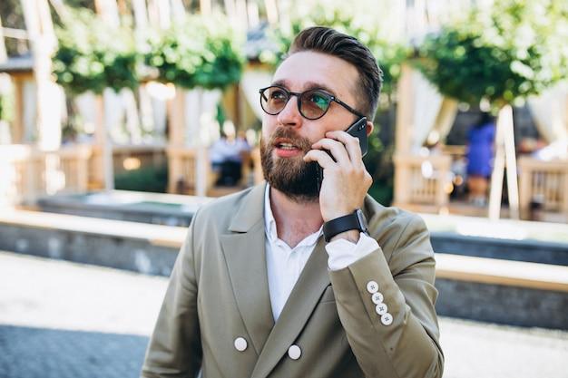 Junger hübscher geschäftsmann, der telefon verwendet