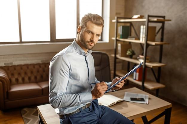 Junger hübscher geschäftsmann, der unterschrift auf dokument in seinem eigenen büro setzt. er schaut vor der kamera lächeln und posieren. selbstbewusster sexy mann.