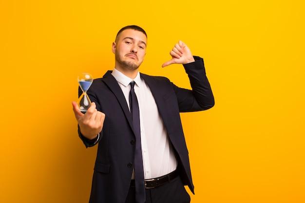 Junger hübscher geschäftsmann gegen flache wand mit einem sanduhr-timer