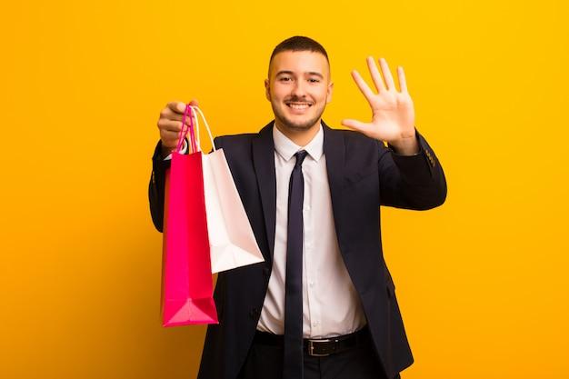 Junger hübscher geschäftsmann gegen flachen hintergrund mit einkaufstaschen