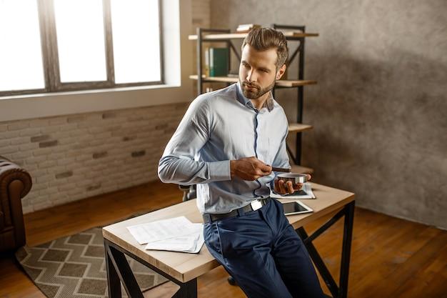 Junger hübscher geschäftsmann halten zigarre und posieren in seinem eigenen büro. er schaut zur seite und setzt sich auf den tisch. zuversichtlich sexy alfa männlich.