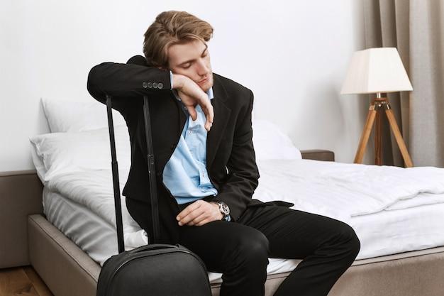 Junger hübscher geschäftsmann im schwarzen anzug schläft mit koffer im hotelzimmer nach langer reise im flugzeug auf geschäftsmission ein.