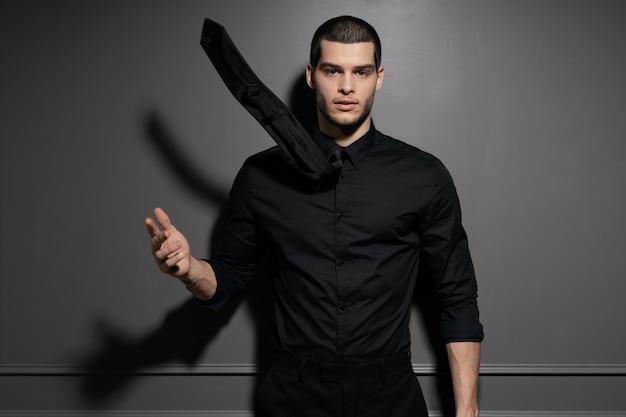 Junger hübscher geschäftsmann im schwarzen hemd