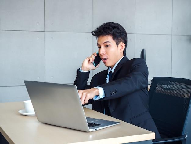 Junger hübscher geschäftsmann in anzug und krawatte, der auf laptop-computer auf seinem schreibtisch mit aufregend und schockierend schaut, während er mit seinem handy im büro auf grauer wand anruft.